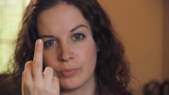 CU Portrait of young woman showing obscene gesture / Madison, Florida, USA