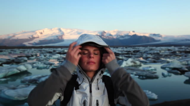 MS Portrait of young woman with glacial lagoon in background, Hofn, Iceland