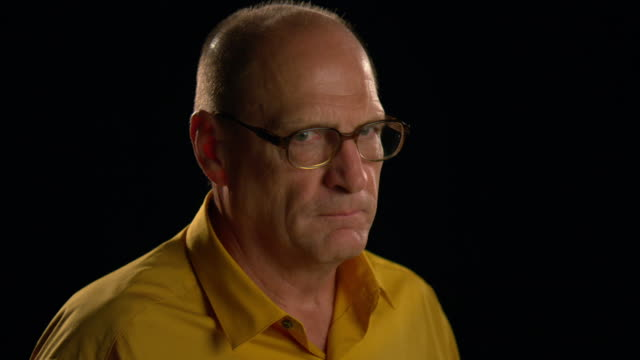 CU portrait senior, bald man with glasses on black background looks up to camera and coughs