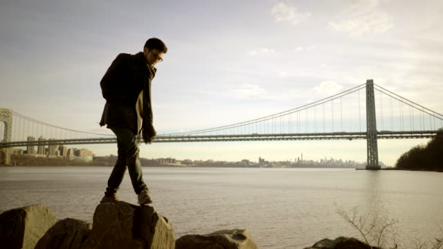 Portrait Shot of Young Asian Man Looking at Water and Bridge. Cityscape in the Background.