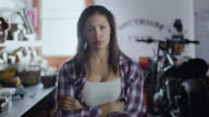 Portrait. Tough female mechanic brushes off hands and crosses arms in motorcycle repair shop.