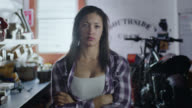 SLO MO Portrait. Tough female mechanic cleans hands and crosses arms in motorcycle repair shop.