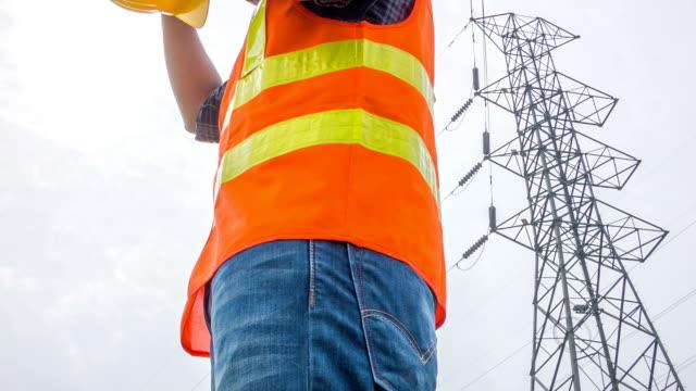 HD kraan: Portretten elektrische werknemer stand naast elektrische toren
