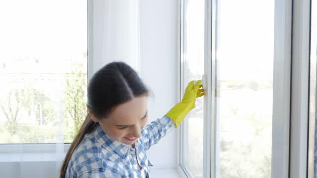 Positive woman washing window