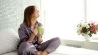 Positively smiling and fully rested female drinking a cup of tea
