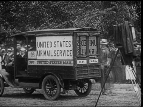 Post Office official 'Air Mail Service' truck w/ people standing behind fence BG men stuffing mail bags into biplane President Woodrow Wilson talking...