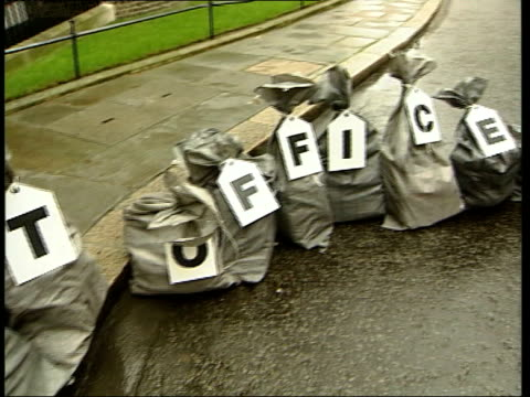 Post Office petition amidst closure fears dEN HARRY SMITH London Downing Street EXT Men putting postal sacks containing petitions down outside Number...