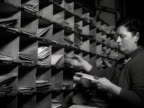 Postal workers place letters into pigeon holes at a postal sorting office