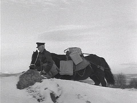 A postman uses a horse to deliver Christmas parcels in a snowy valley in the Scottish highlands