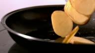 Potato wedges falling in a hot pan