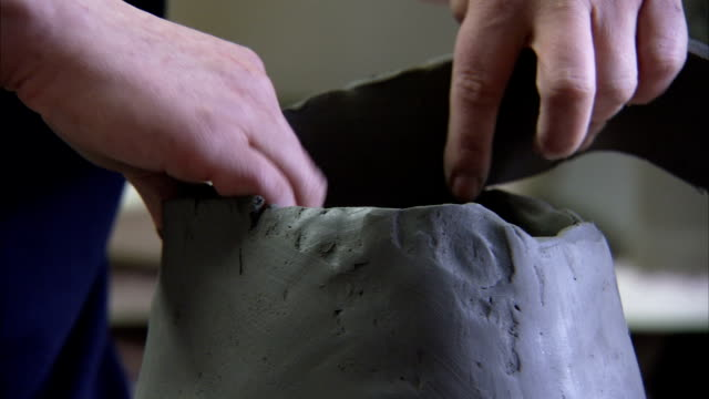 A potter adds clay to a pot. Available in HD.