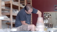 MS potter in pottery studio at pottery wheel reaches with his arm into tall vase while shaping / Palm Springs, California, USA