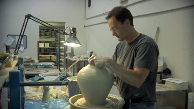 MS DS Potter putting finishing touches on pot at pottery studio / Windsor, Vermont, USA