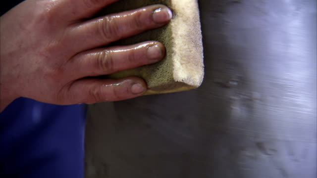 A potter smooths a clay vase with a sponge. Available in HD.