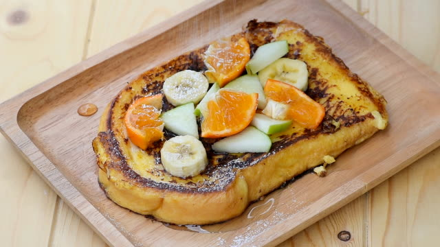 Pour the icing sugar on French Toast with Banana, Apple and Orange
