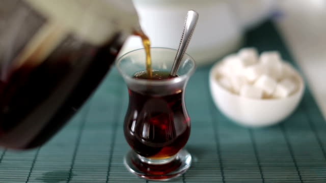Pouring and stirring cup of traditional Turkish tea - chai