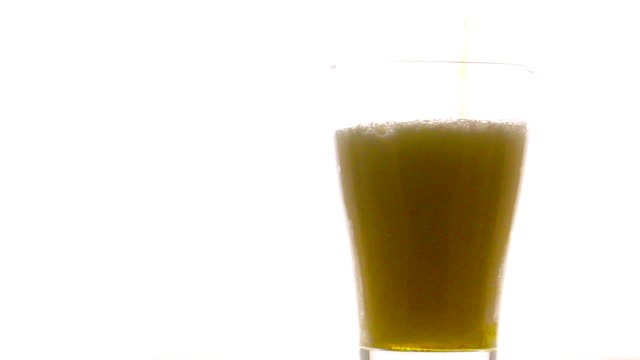 Pouring beer into rotate glass on white background