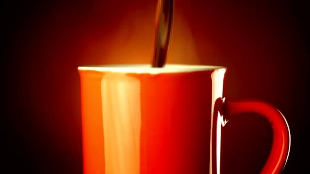 Versare nero in una tazza di caffè.