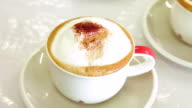 Pouring brown sugar into a cup of cappuccino coffee.
