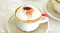 Eingießen Brauner Zucker in eine Tasse cappuccino Kaffee.