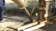Pouring cement in construction site.