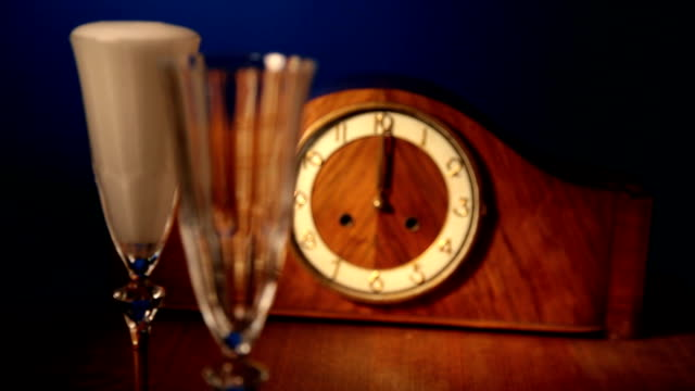 Pouring champagne, antique clock strikes twelve.
