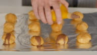 Pouring chocolate sauce over the profiteroles