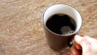 gießt Kaffee in eine Tasse auf Holztisch