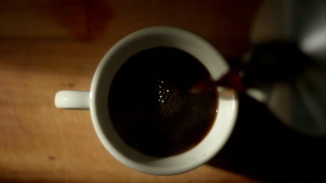 Koffie voor een kopje met natuurlijke stoom daarop gieten