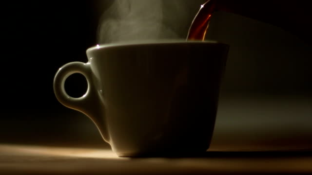 Pouring coffee to a cup with natural steam on it