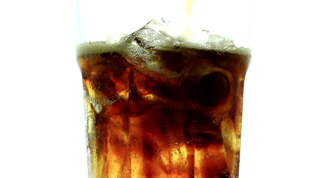 Pouring Cola into glass with ice on white