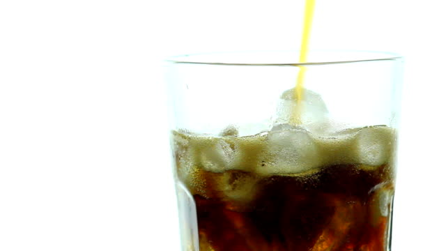 Pouring Cola into rotate glass with ice on white