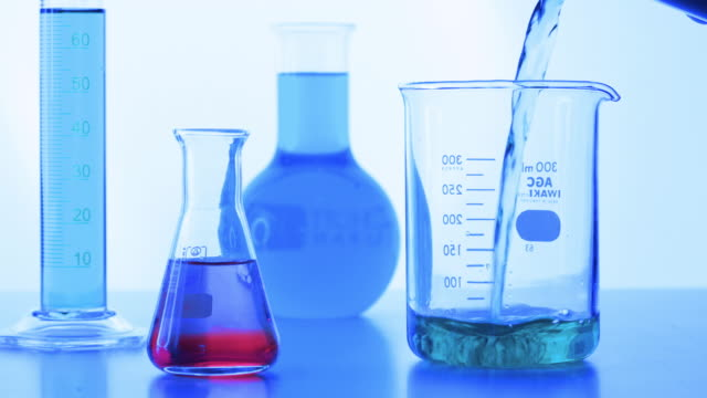 Pouring color liquid into laboratory grassware