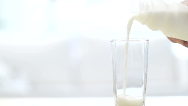 Pouring glass of fresh milk