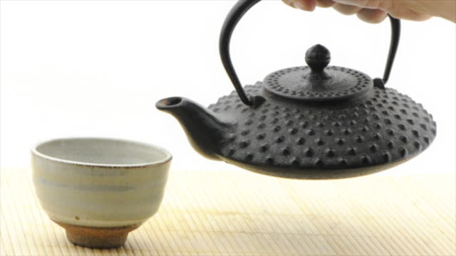 Pouring green tea from tetsubin pot - white background (HD720p)