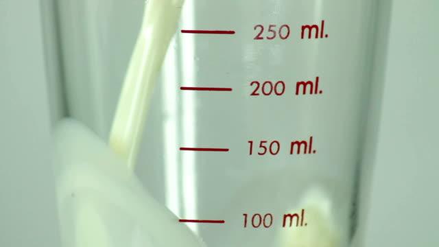 Gießen Milch in Glas