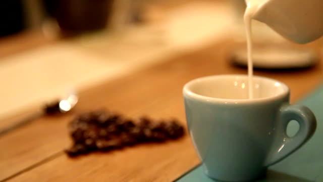 Gießen Milch in Kaffee von barista