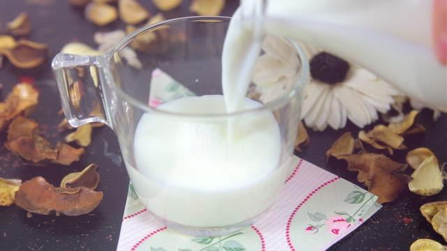 Gießen Milch in eine Tasse auf vintage-Tisch.