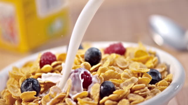 SLO MO PAN Pouring milk over berries and corn flakes