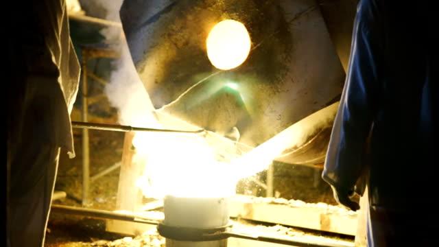 SLO MO Gießen von flüssigem Metall in Gussteilen und geschichteten weißer Rauch aus Hochöfen. Verarbeitung von Stahl in Eisengießerei Pflanze.