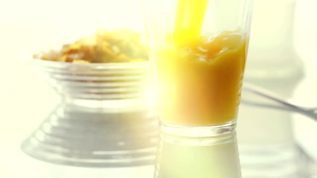 Pouring orange juice at breakfast, slow motion  DR FO