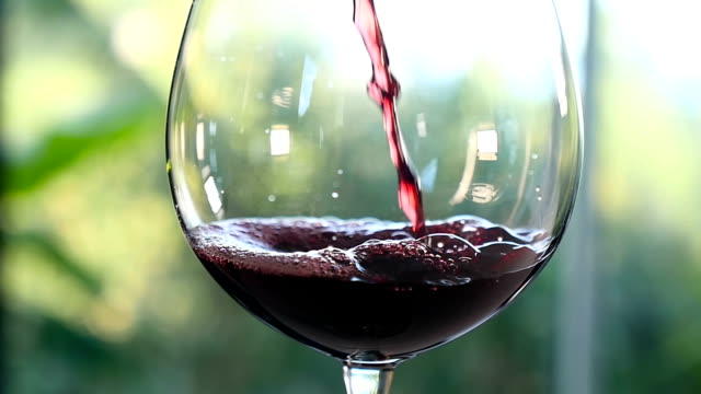 Pouring red wine in wineglass