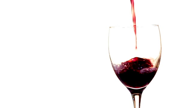 Versare il vino rosso al rallentatore/isolato su bianco