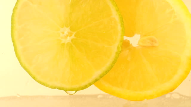 pouring soda water over lemon and lime slices white background
