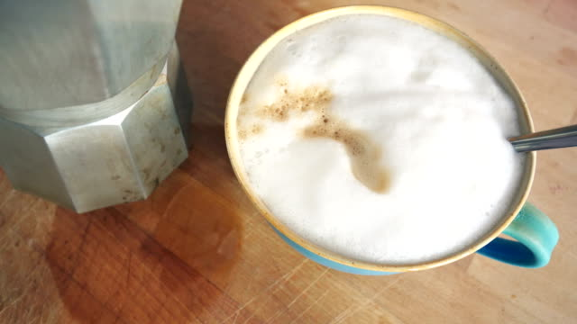 Pouring some coffee in a cup already full with milk foam