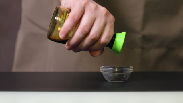 Pouring soy sauce in a glass bowl.
