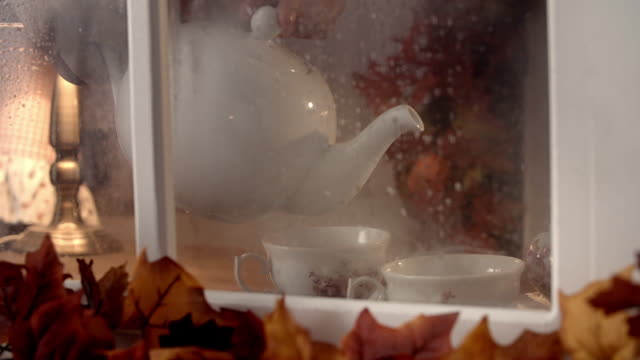 Pouring Tea into cup on Autumn Day