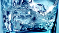 Pouring water into a glass with cubes of ice.