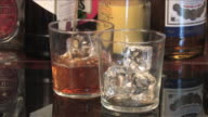 Pouring whiskey over ice into tumblers, Spain
