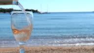 Der Flasche Wein gießen in ein Glas
